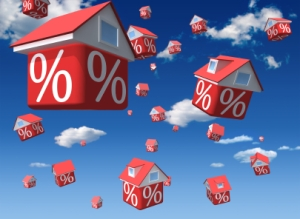 Falling houses with percent symbol on sky background